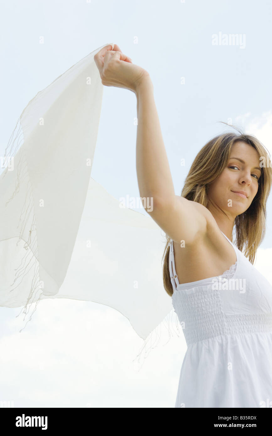 Woman standing outdoors, holding up shawl, low angle view - Stock Image