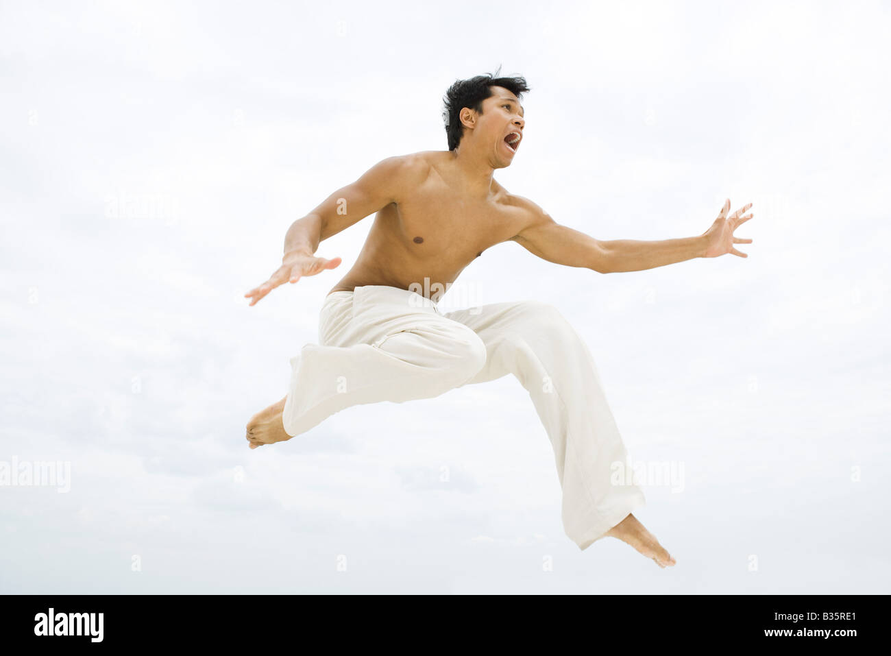 Man leaping in the air, side view - Stock Image