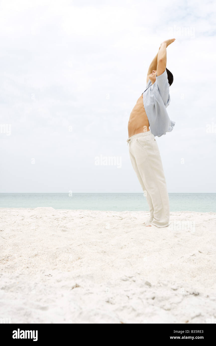 Man standing in sun salutation pose on beach, side view - Stock Image