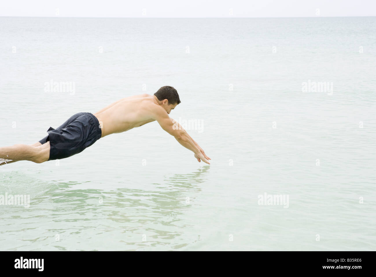 Man diving into the ocean, side view - Stock Image