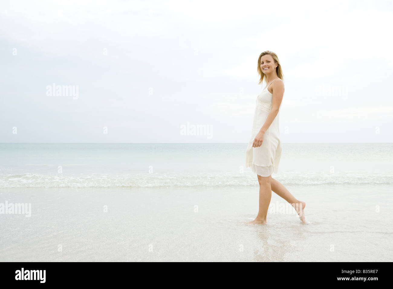 Woman walking at the beach in the surf, smiling at camera - Stock Image