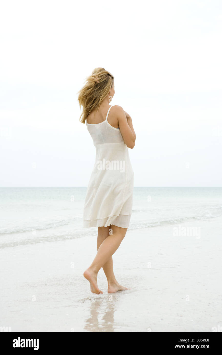Woman walking at the beach in the surf, rear view - Stock Image