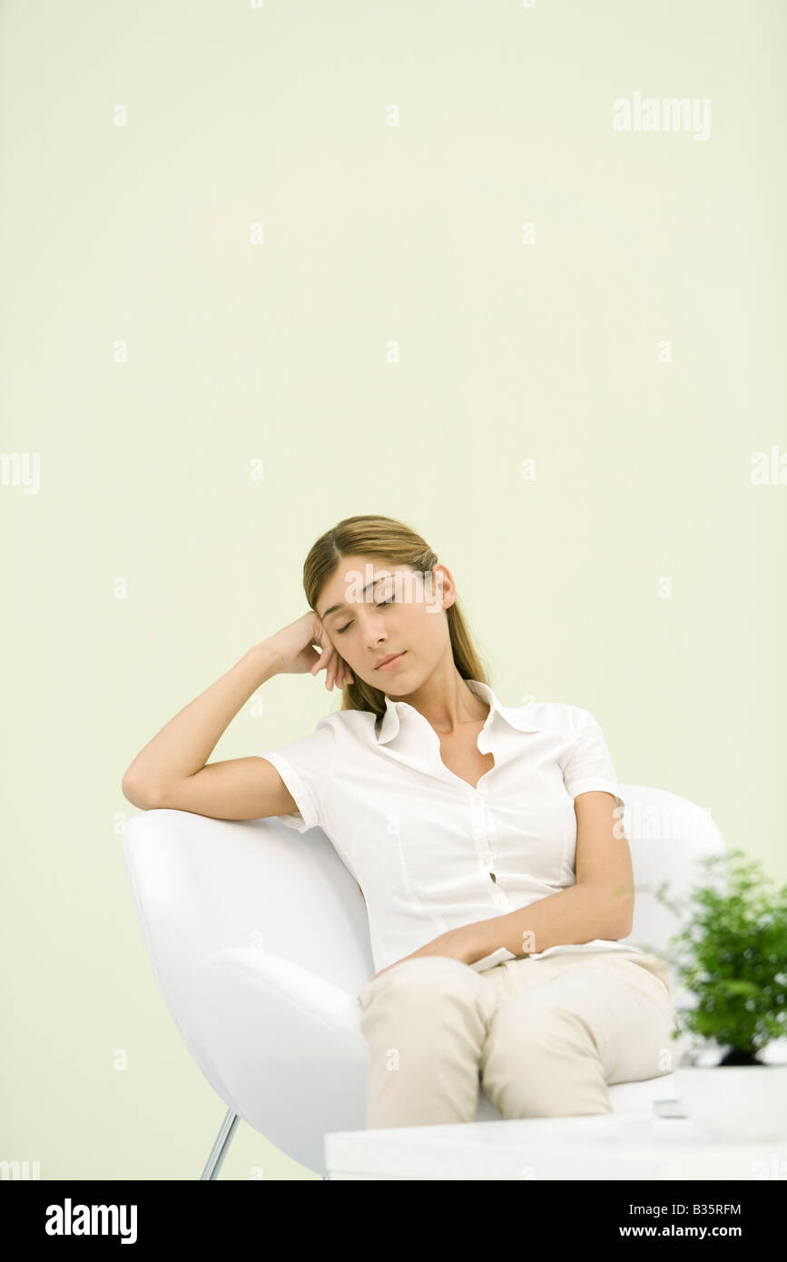 Woman sitting in chair, leaning against elbow, eyes closed - Stock Image