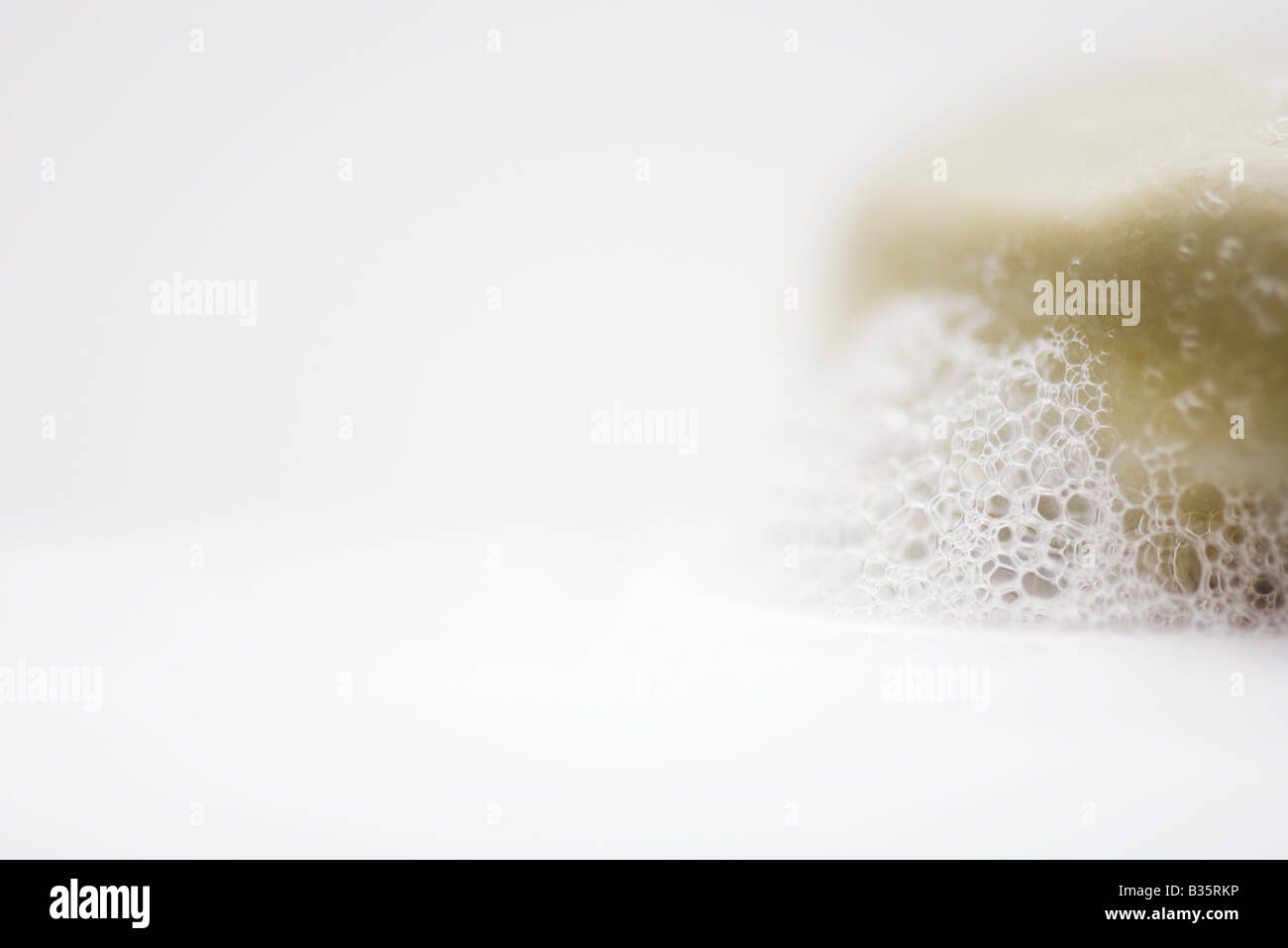 Bar of soap and suds, close-up - Stock Image