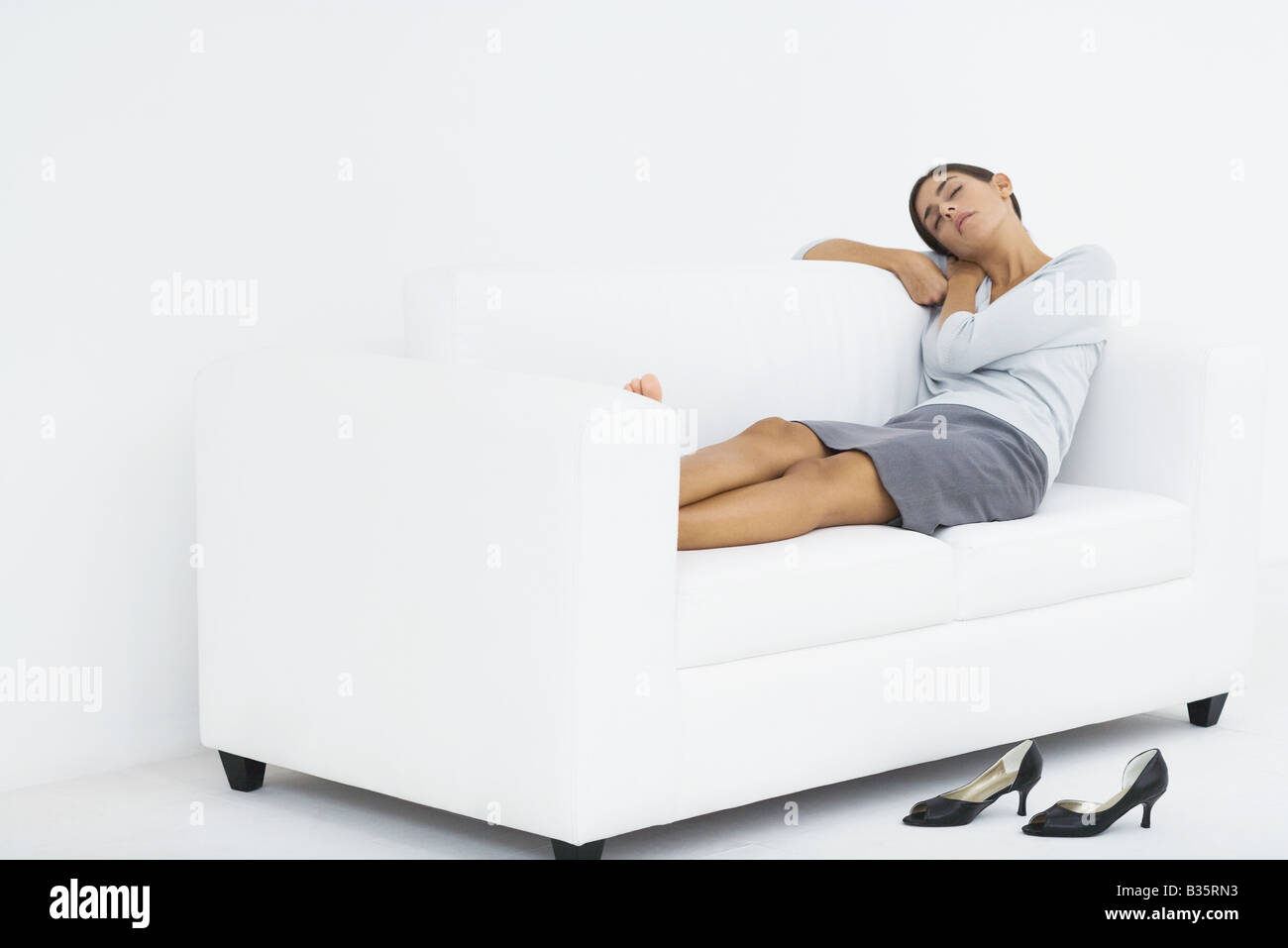 Woman reclining on couch, resting head on her arms, eyes closed Stock Photo