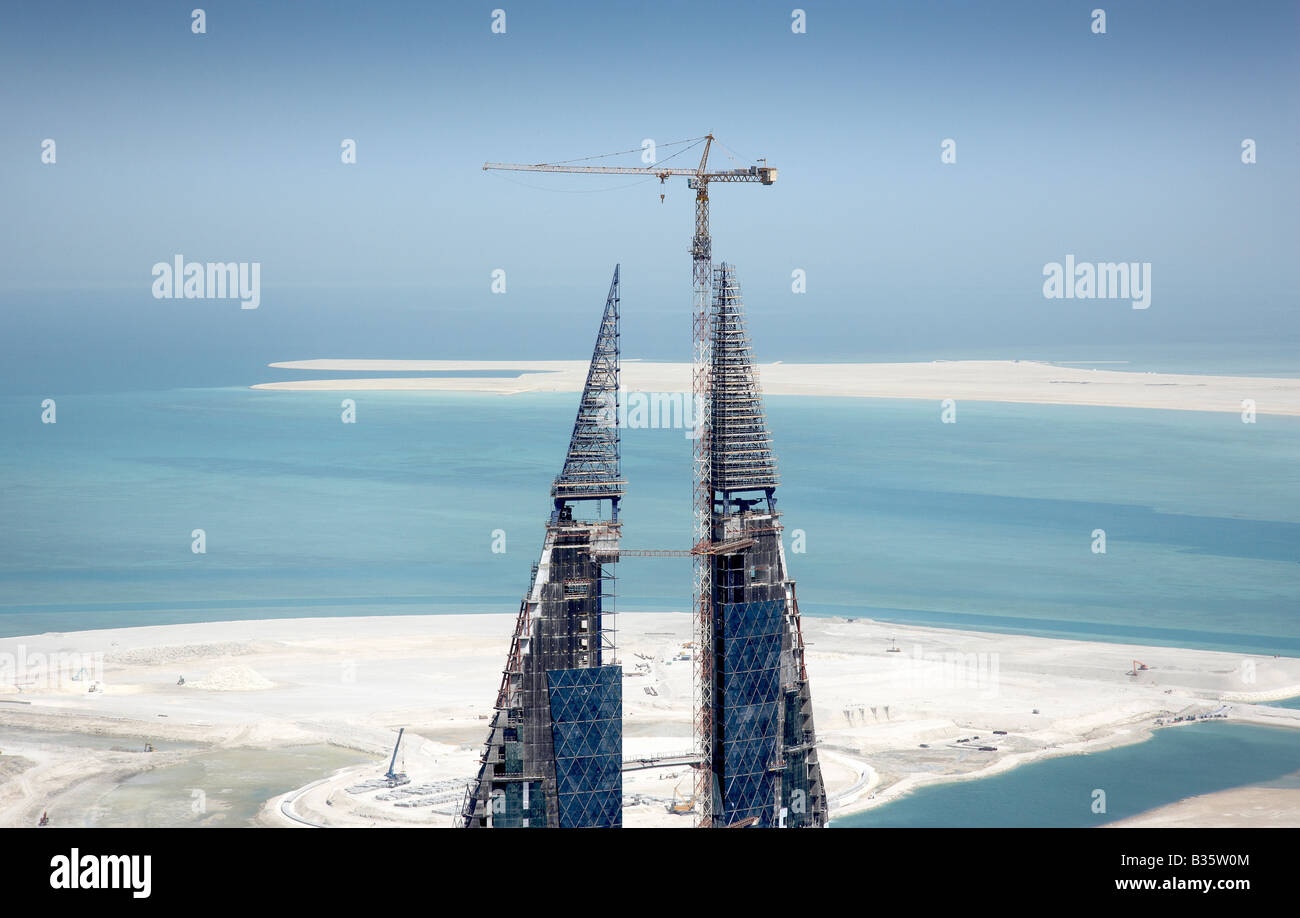 High crane towers over the Bahrain World Trade Centre Center, Manama. New twin towers built on reclaimed land. - Stock Image