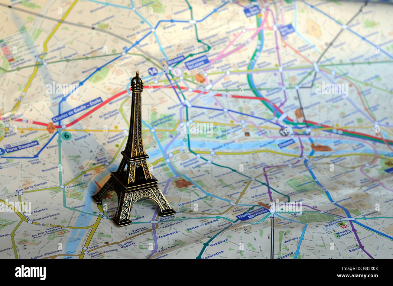 A Small Scale Model Of The Eiffel Tower Standing On A Map Of Paris