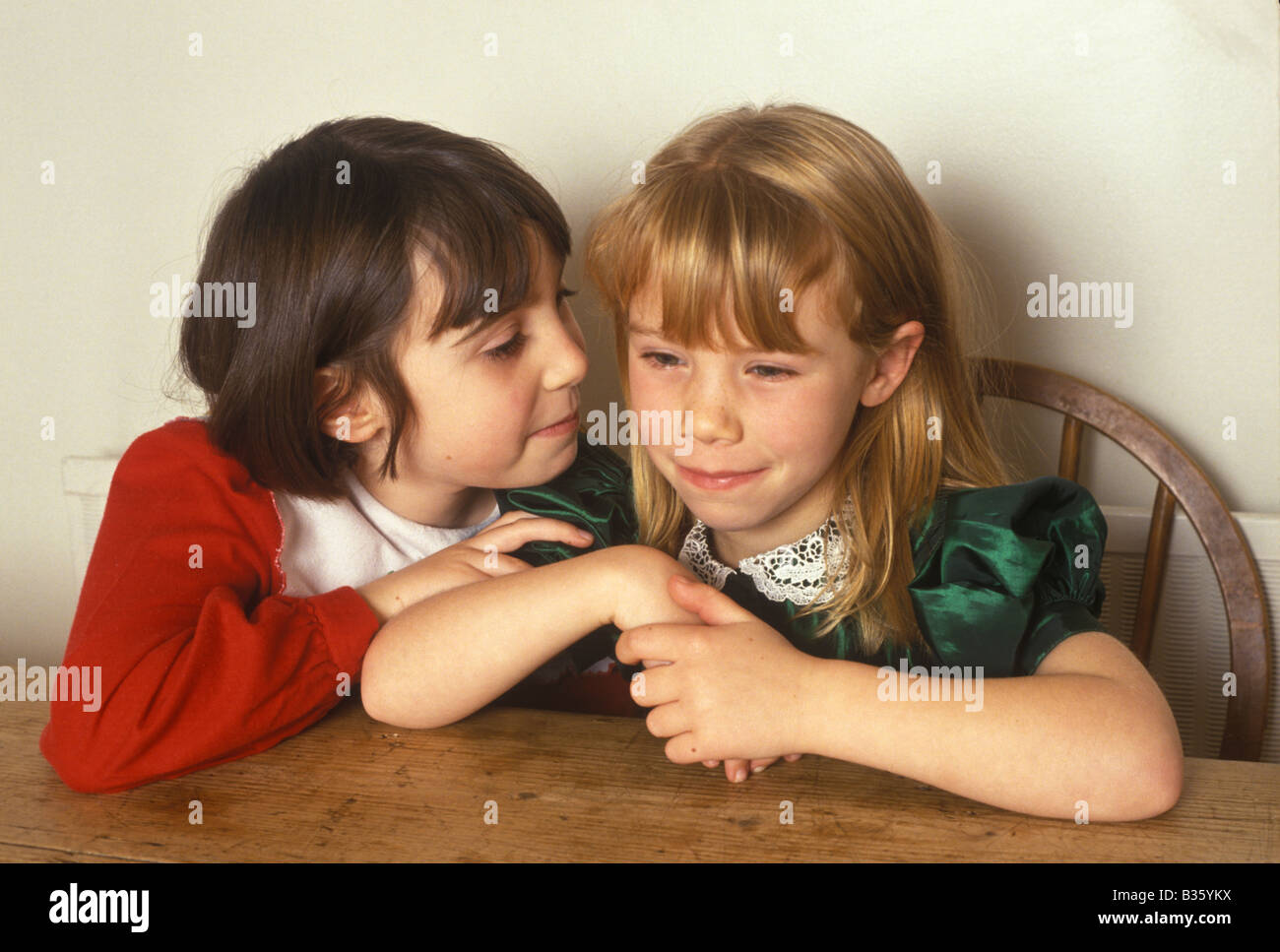 children whispering to each other - Stock Image