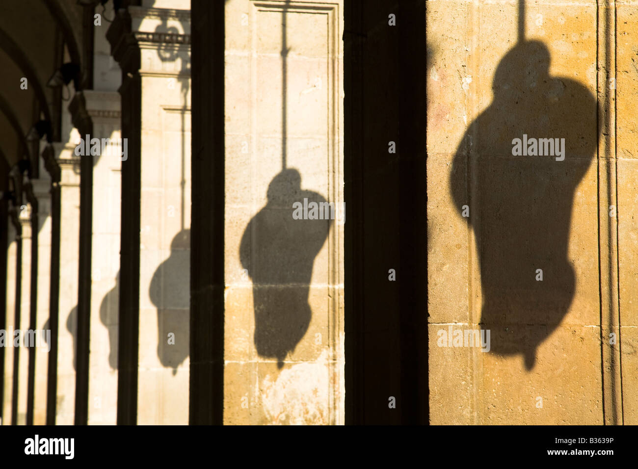 SPAIN Barcelona Repeating shadows of hanging lamps on columns in Placa Reial Neoclassical square plaza - Stock Image