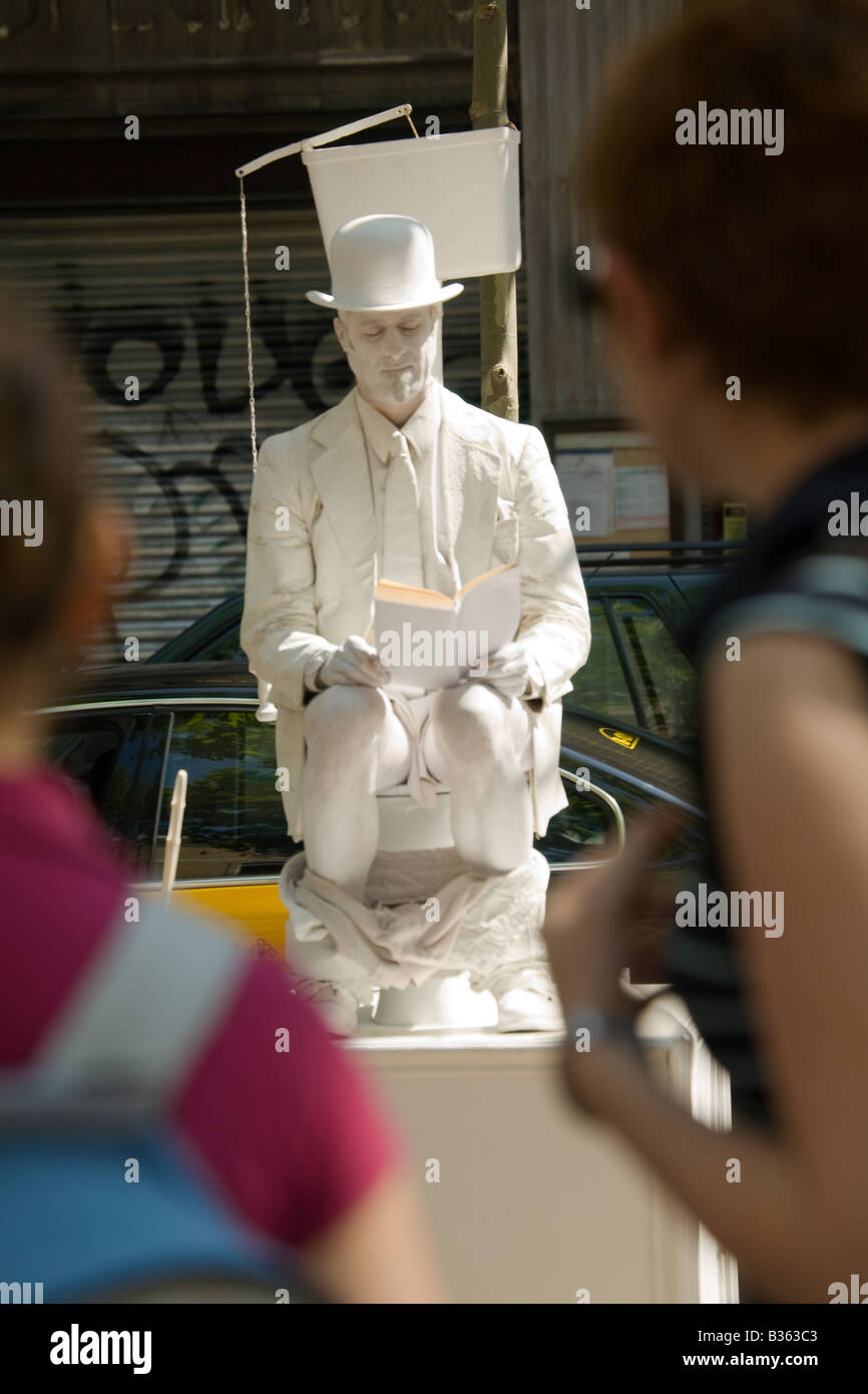 SPAIN Barcelona Male street artist and performer in white makeup sit on toilet on the Ramblas two people passing - Stock Image