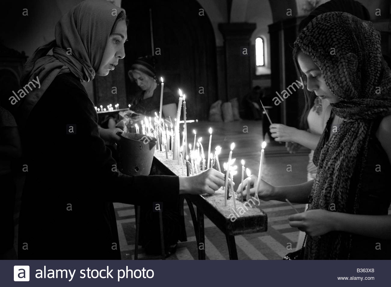 Locals lighting candles The Holy Trinity Cathedral commonly known as The Sameba cathedral in Tbilisi, Republic of - Stock Image