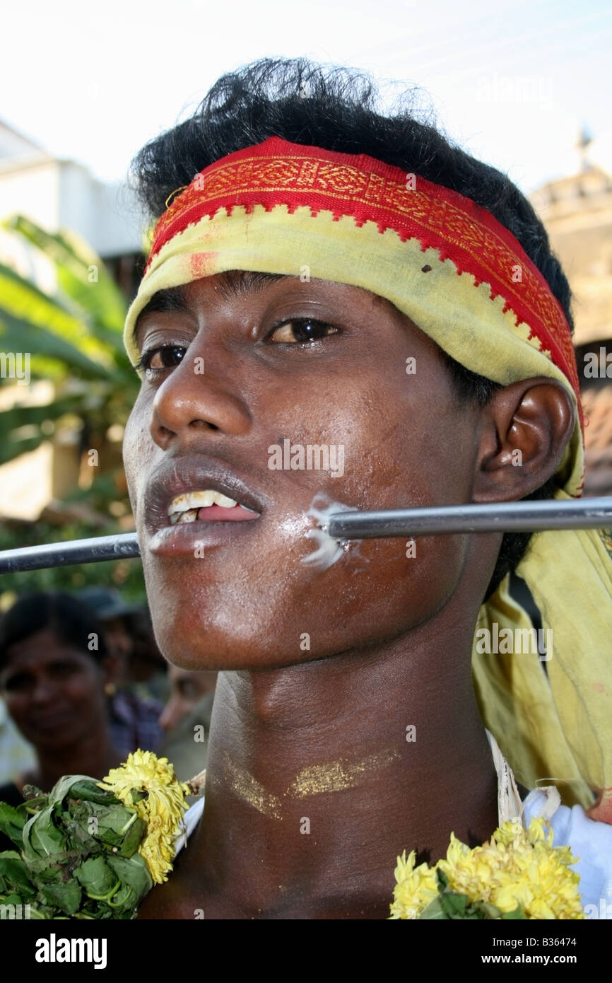 Man parades the street with a large spear through his cheeks in a form of self sacrifice worship to the goddess - Stock Image