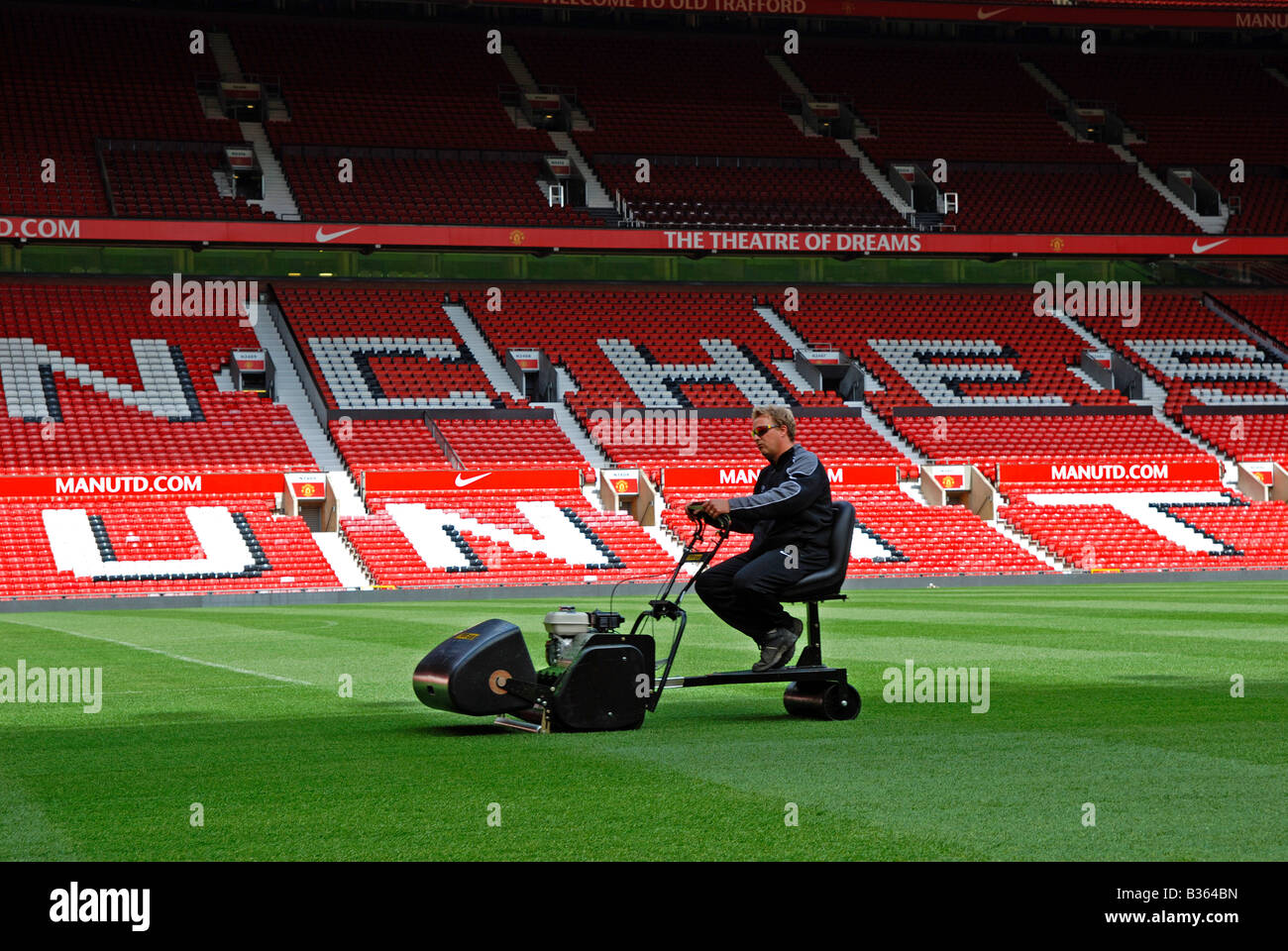 a groundsman cutting the grass at old trafford home of manchester united football club, manchester, england,uk - Stock Image