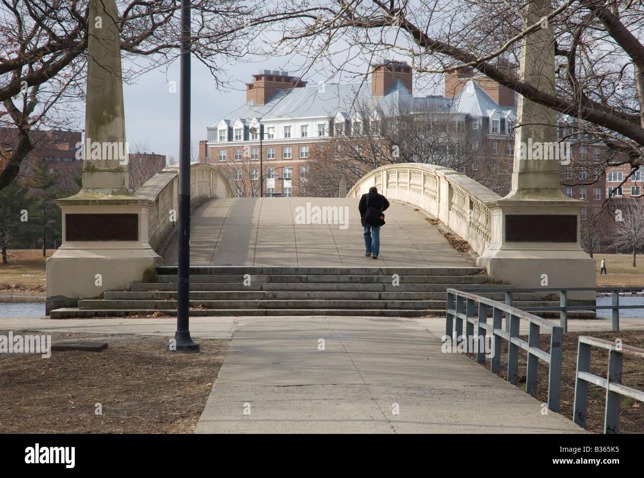 A man crosses the Weeks Memorial Footbridge at Harvard University in Cambridge Massachusetts - Stock Image
