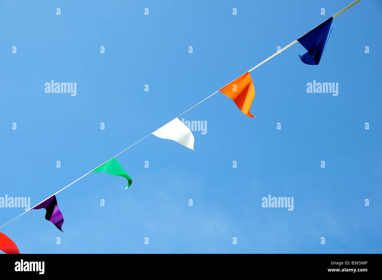 Bunting across a street with a blue background - Stock Image