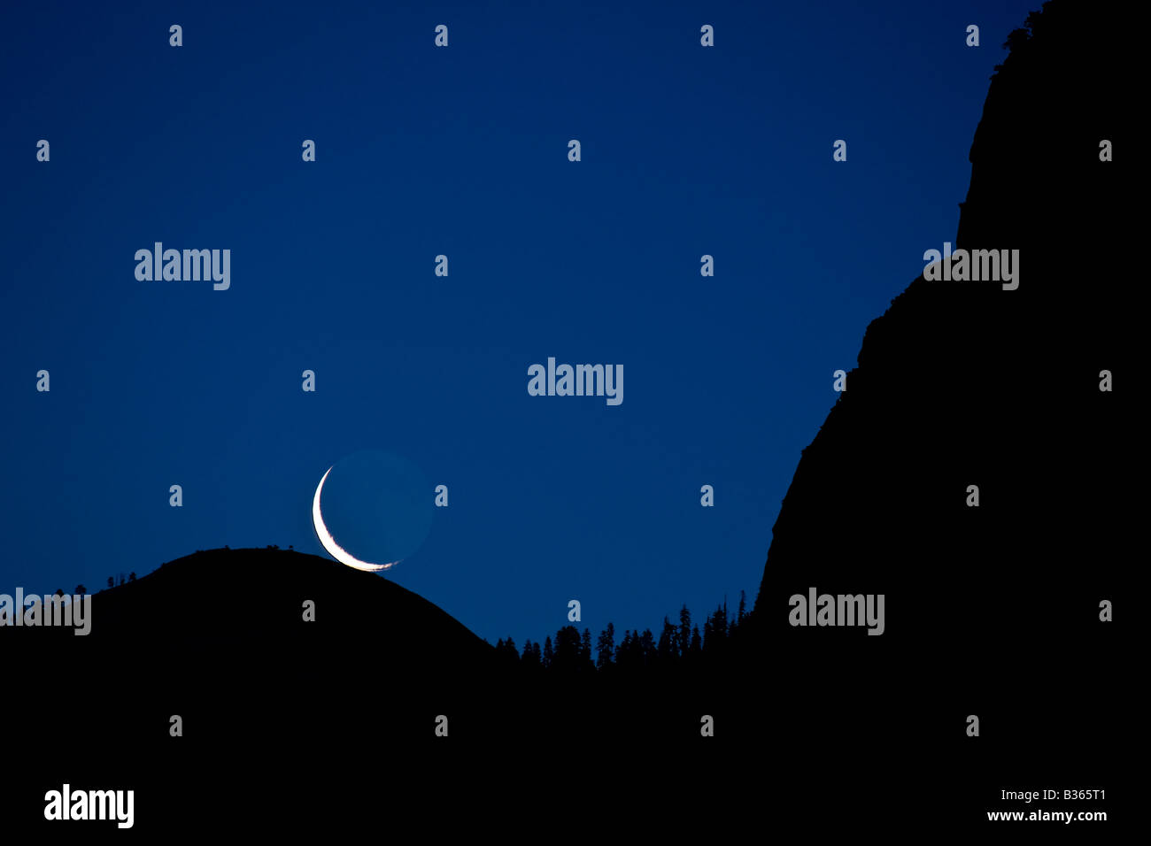 A pre dawn crescent moon rises directly over the top of Sentinel Dome Yosemite National Park California USA - Stock Image