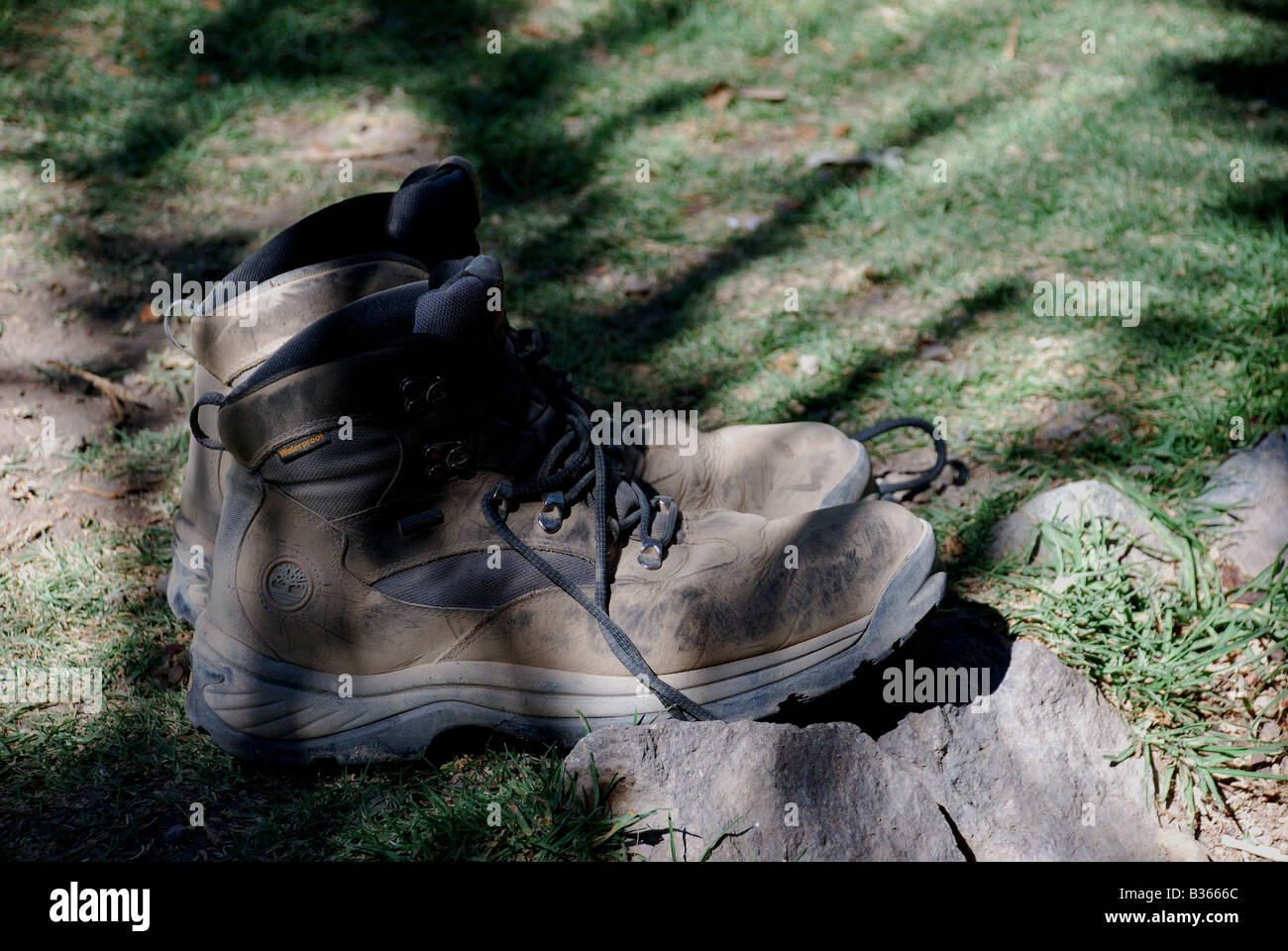 Worn out shoes sitting in sunlight after trek - Stock Image