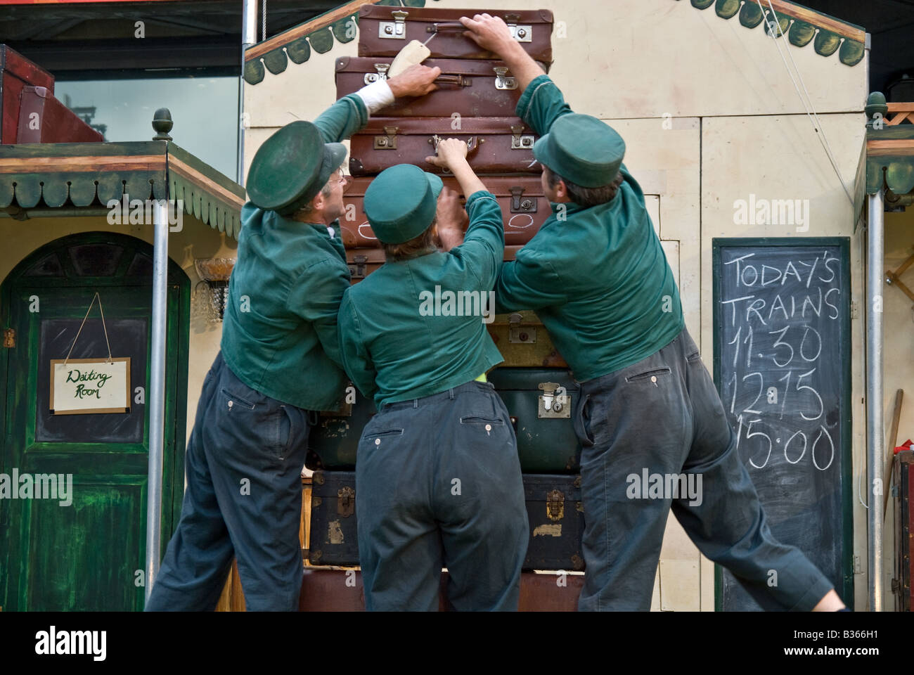 THREE TRAIN WORKERS TRYING TO ORGANIZE THE PASSENGER LUGGAGE IN A BUNGLING WAY - Stock Image