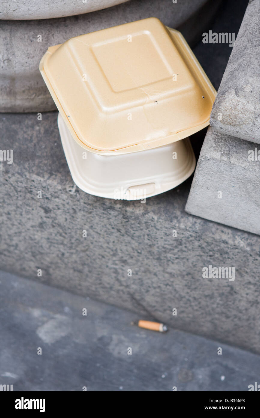 Chip and burger boxes with discarded cigarette the morning after - Stock Image