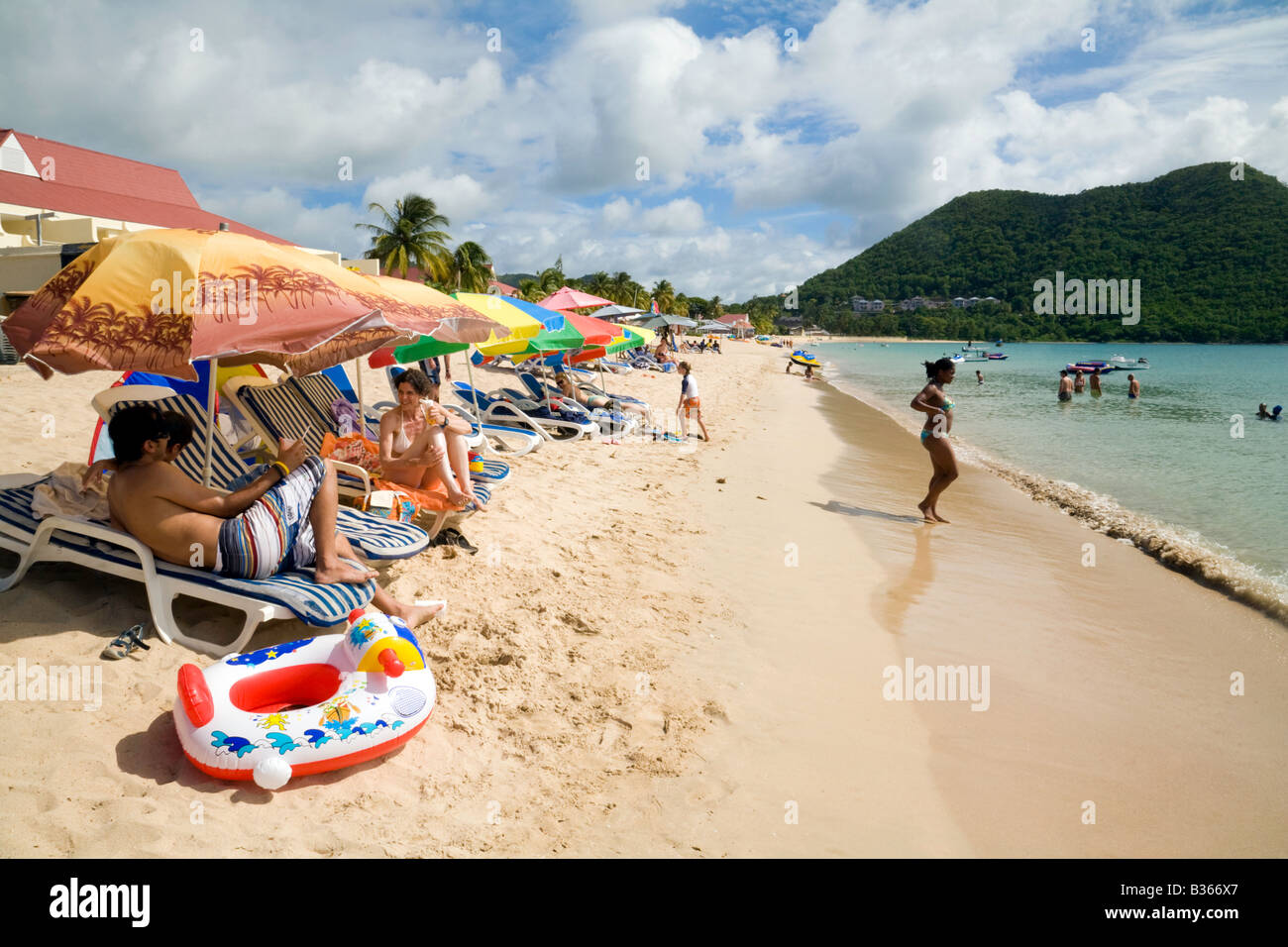 Tourists enjoy the sunshine on Reduit beach, St Lucia, West Indies - Stock Image