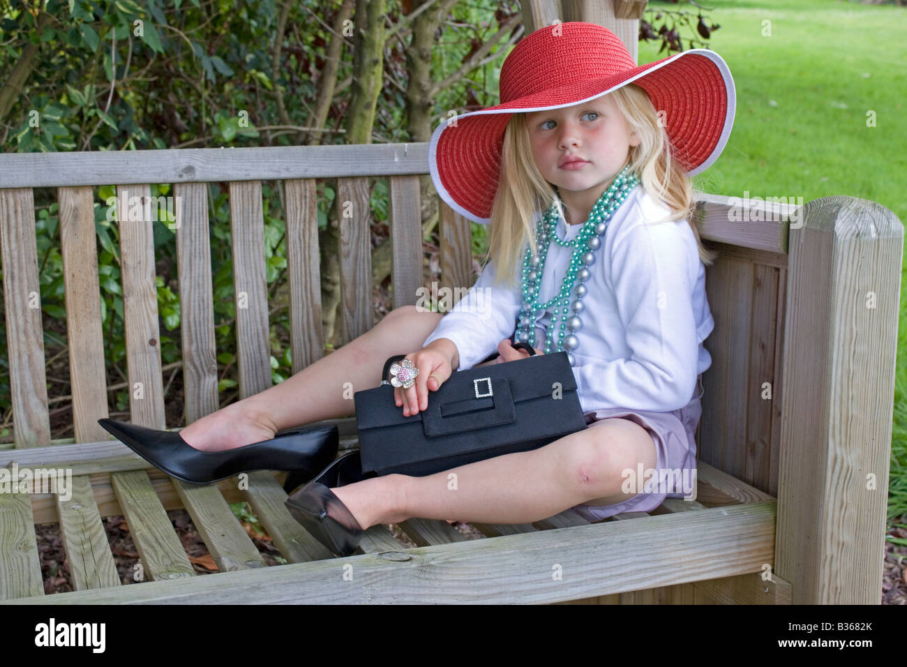 3 year old girl in garden dressing up in grown up clothing - Stock Image