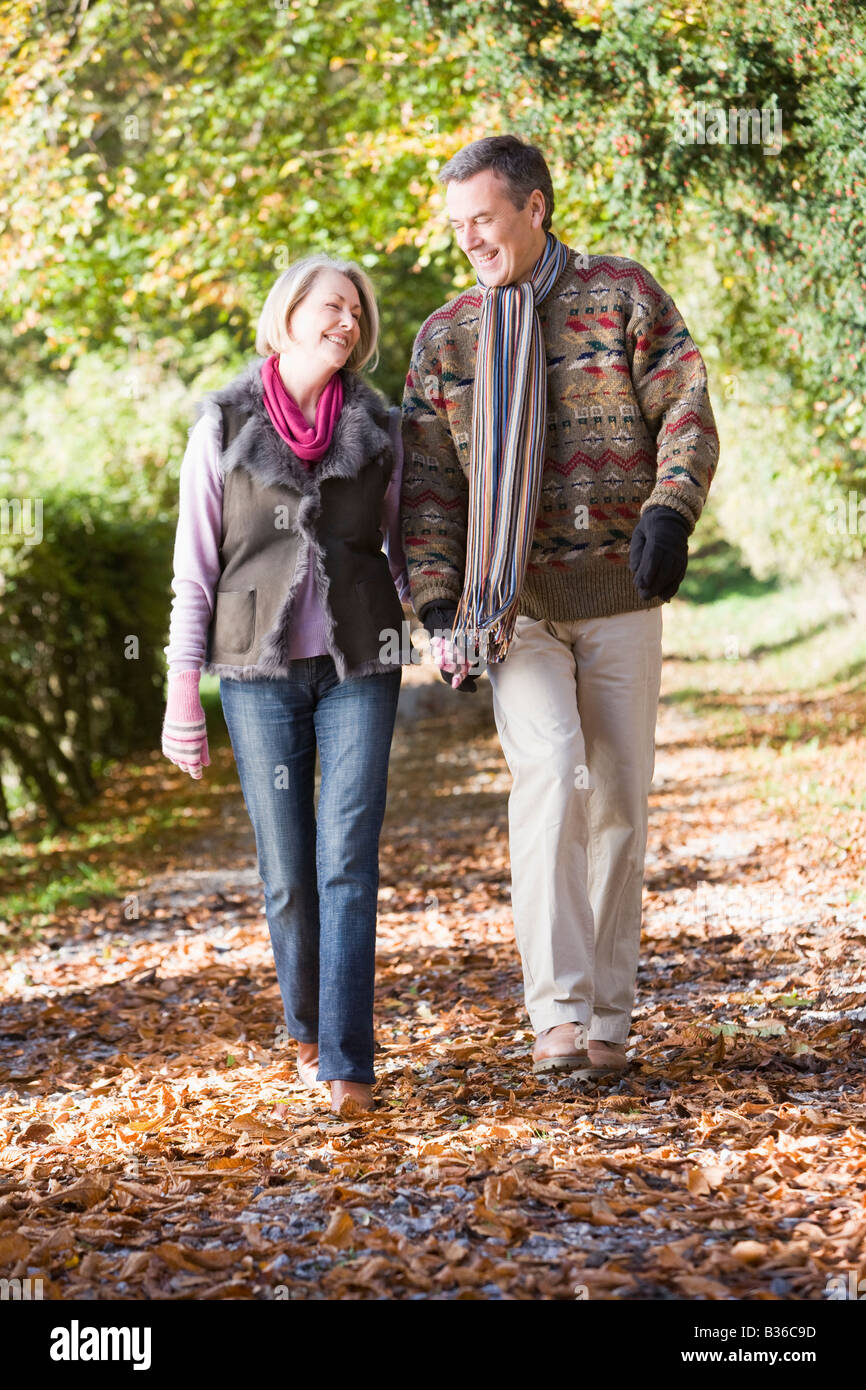 Couple outdoors walking on path in park holding hands and smiling (selective focus) Stock Photo