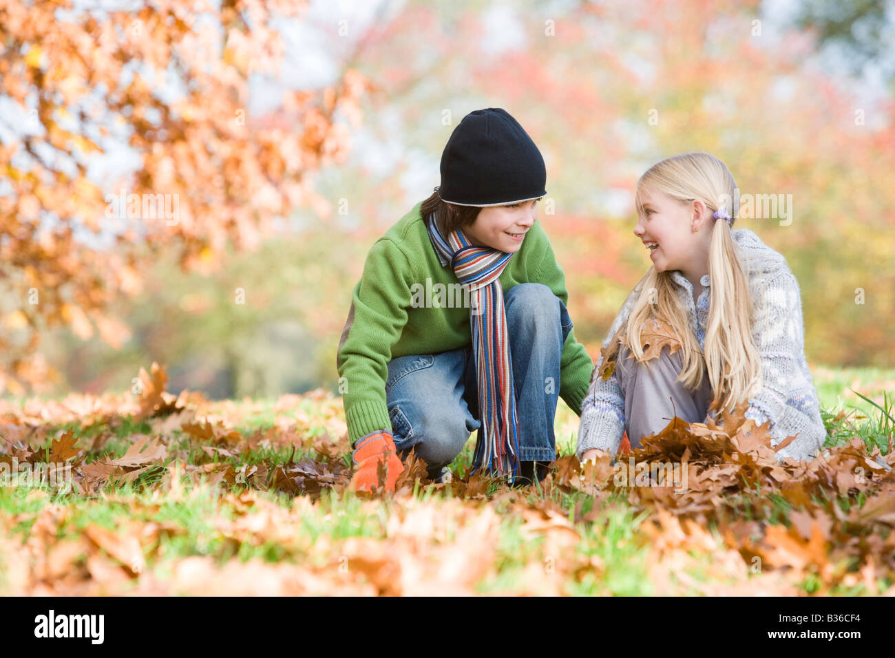 Two young children outdoors in park playing in leaves and smiling (selective focus) Stock Photo