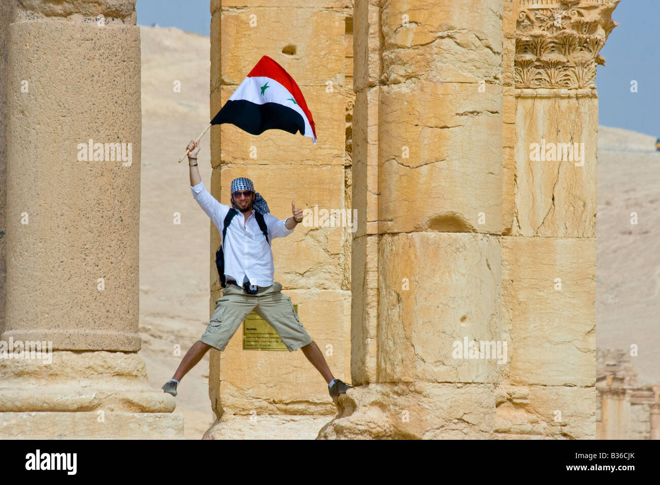 Tourist Waving A Syrian Flag At The Roman Ruins Of Palmyra In Syria