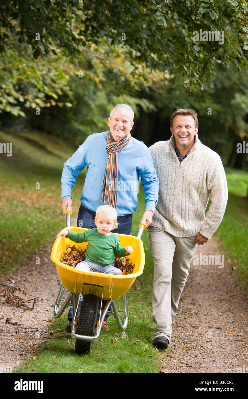 Two men walking on path outdoors pushing baby in wheelbarrow and smiling (selective focus) - Stock Image