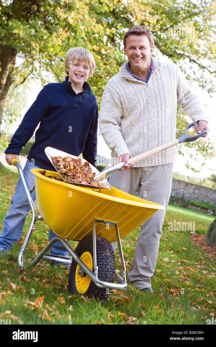 Man outdoors with young boy shoveling leaves into wheelbarrow and smiling (selective focus) Stock Photo