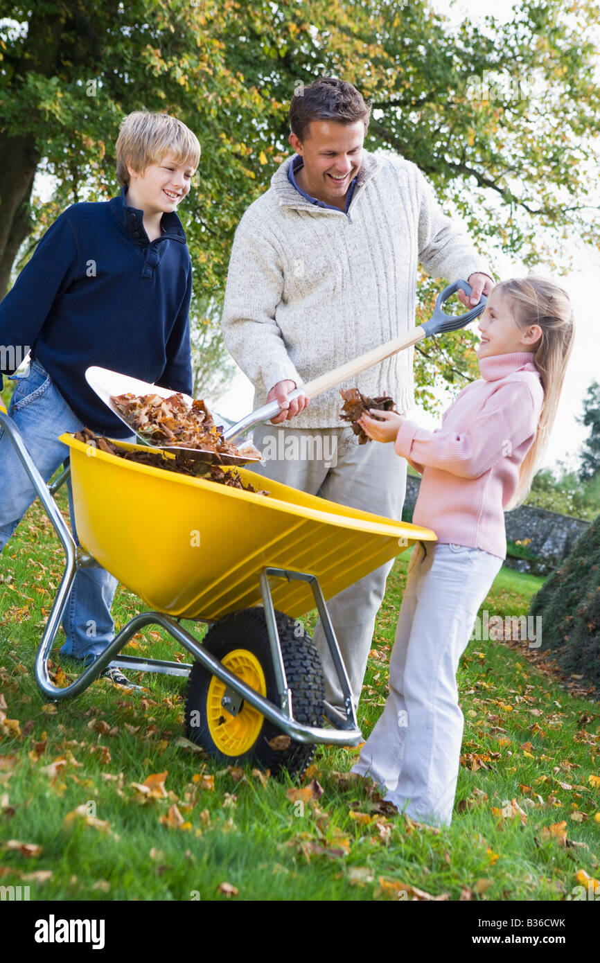 Father outdoors with two young children shoveling leaves into a wheelbarrow and smiling (selective focus) Stock Photo
