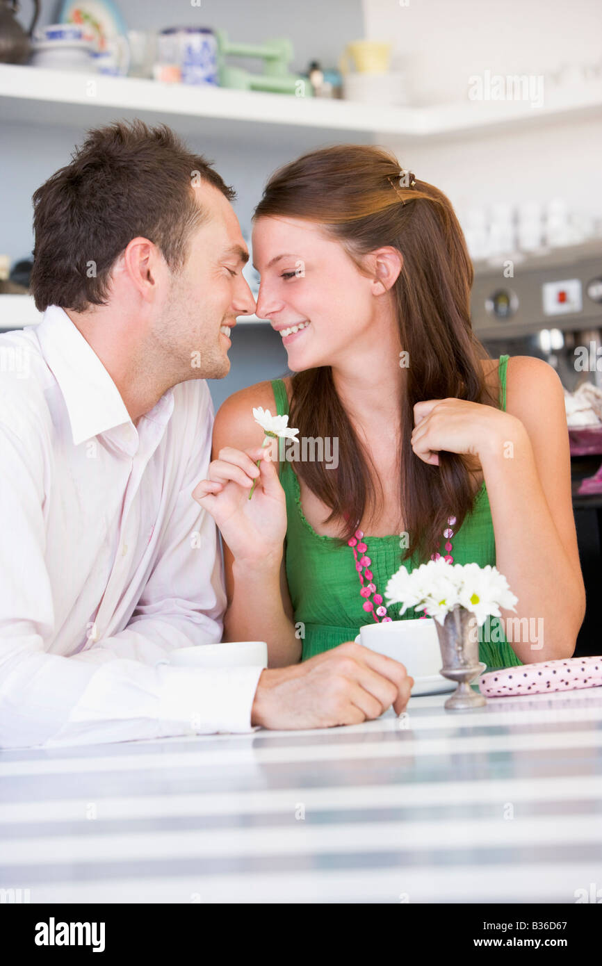 Young couple sitting at a table looking into each other's eyes - Stock Image