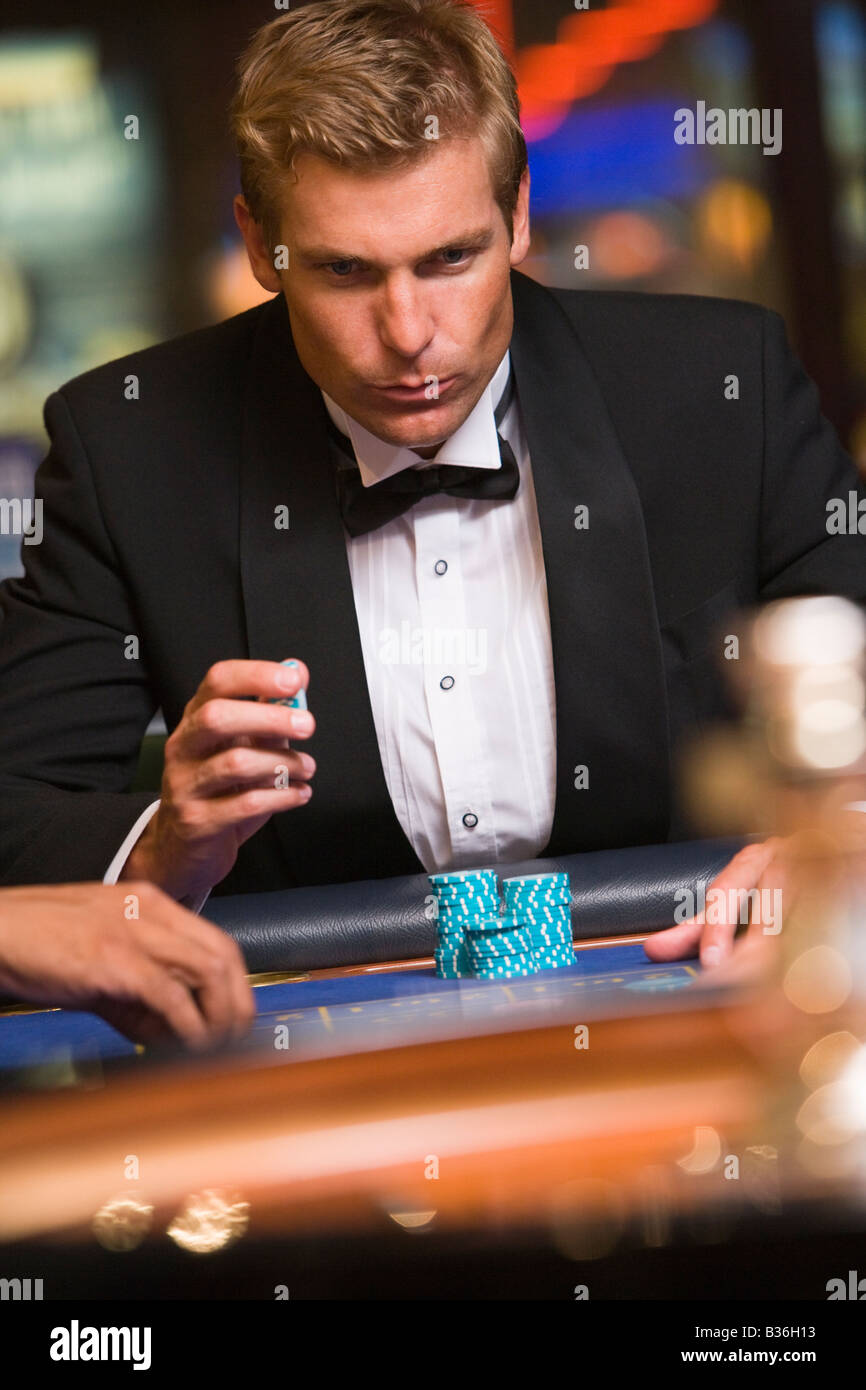 Man in casino playing roulette (selective focus) - Stock Image