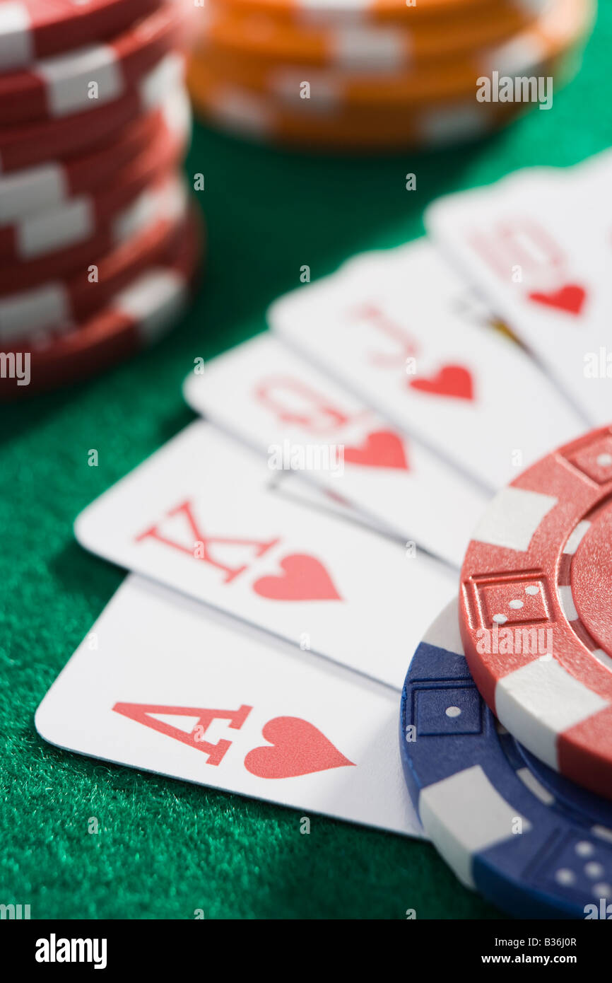 Playing cards making royal flush in hearts by poker chips (close up/selective focus) - Stock Image