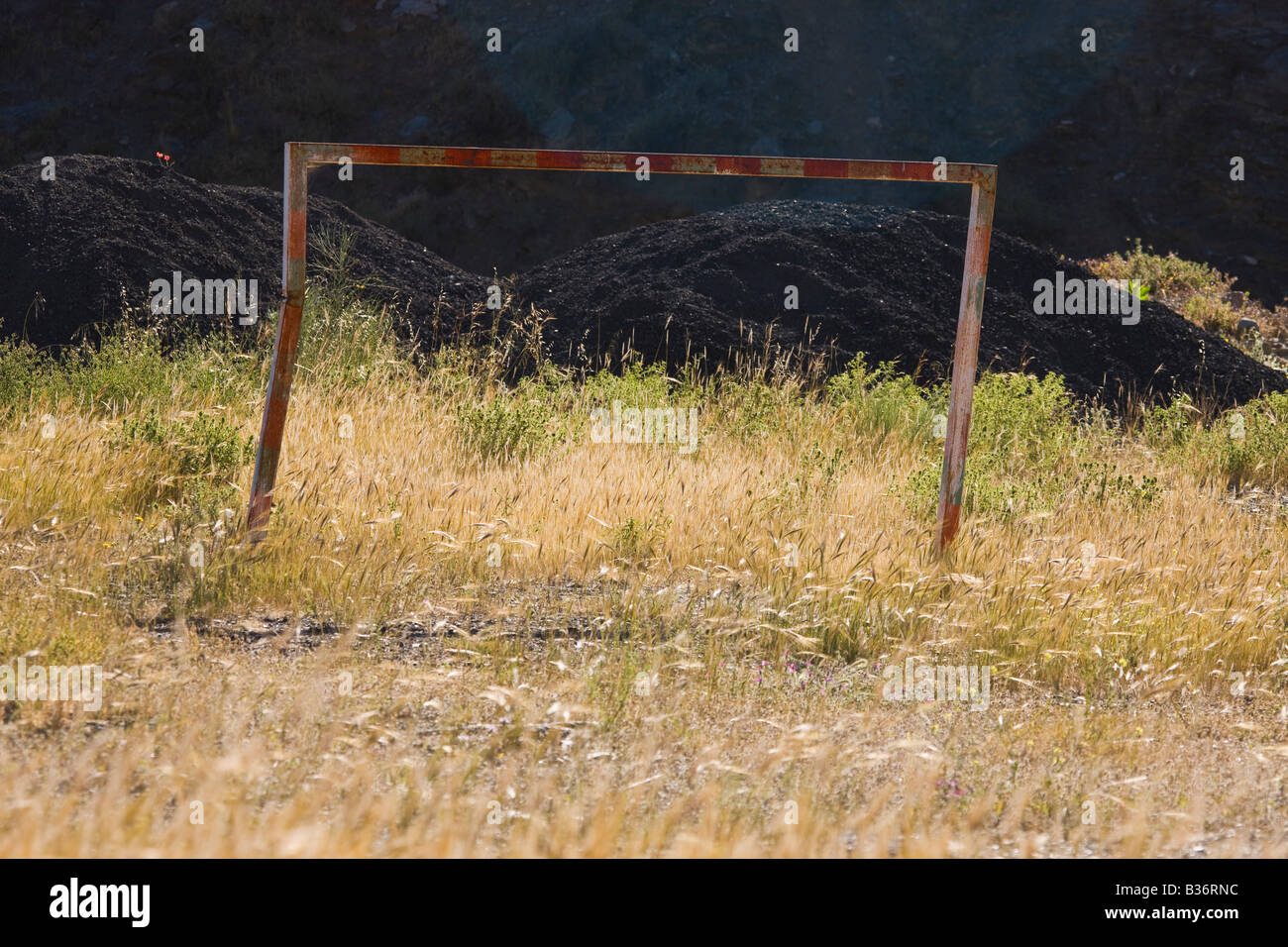 Old battered rusted football goalpost in uncared for field - Stock Image