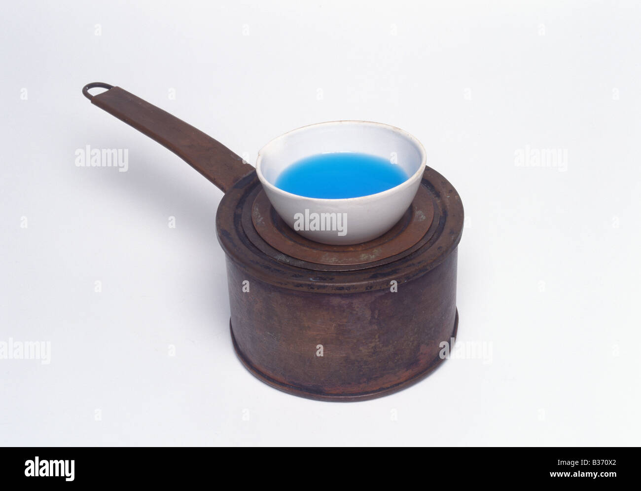 an old style of water bath with an evaporating basin containing copper sulphate solution Stock Photo