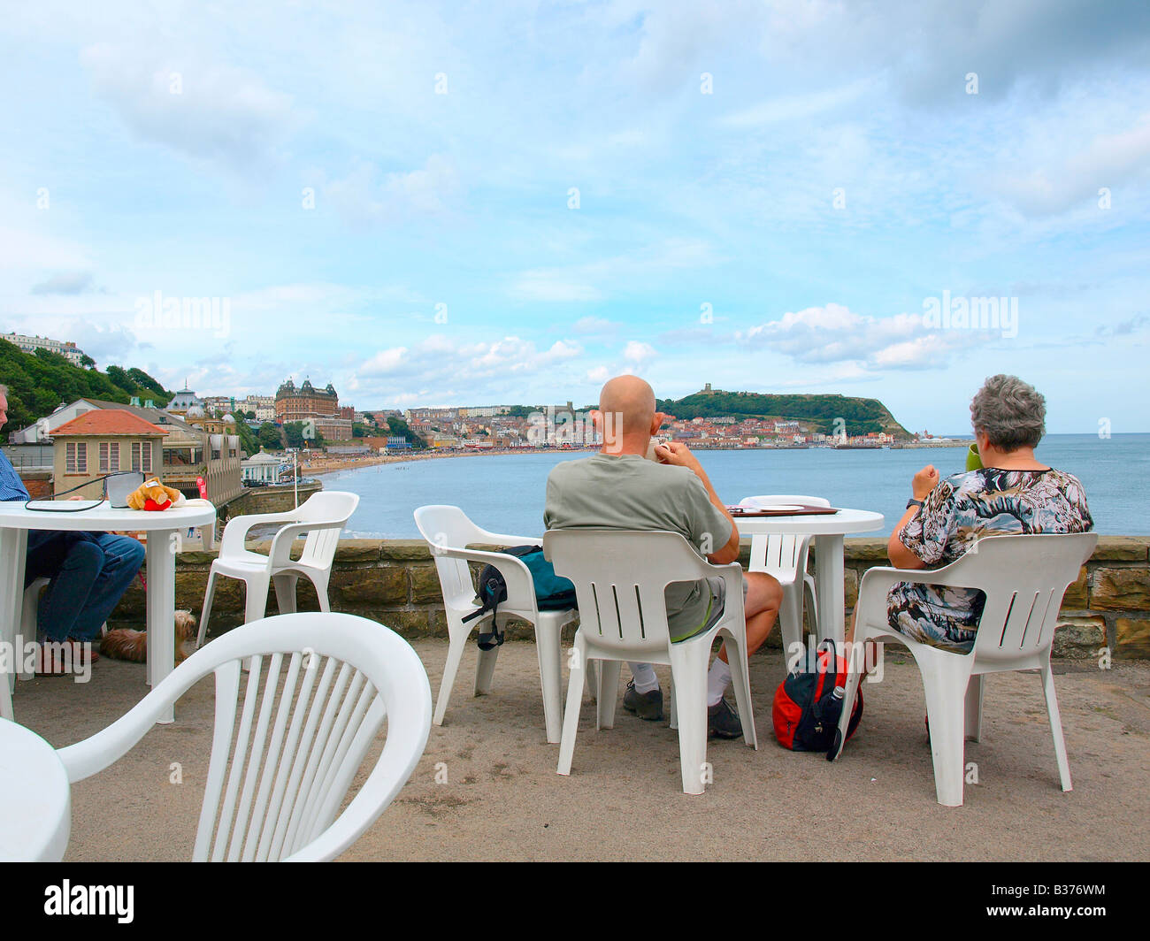 A couple look out across the south bay whilst enjoying a drink at a cafe in Scarborough,Yorkshire,uk. - Stock Image