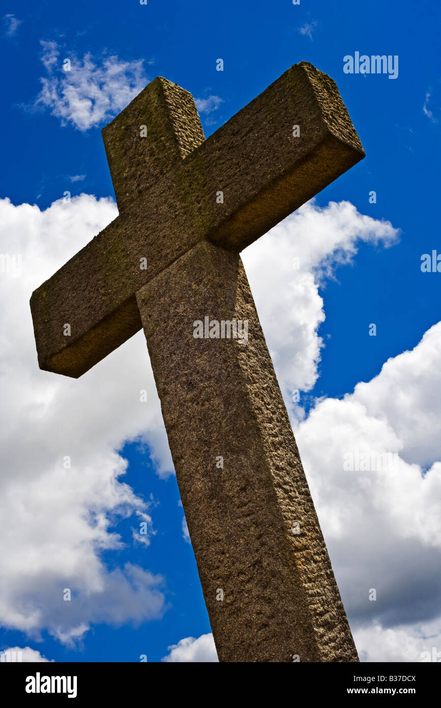 Large stone Christian cross against blue sky in France Europe - Stock Image