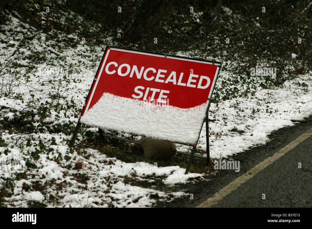 Road sign covered in snow stating concealed Site Entrance - Stock Image