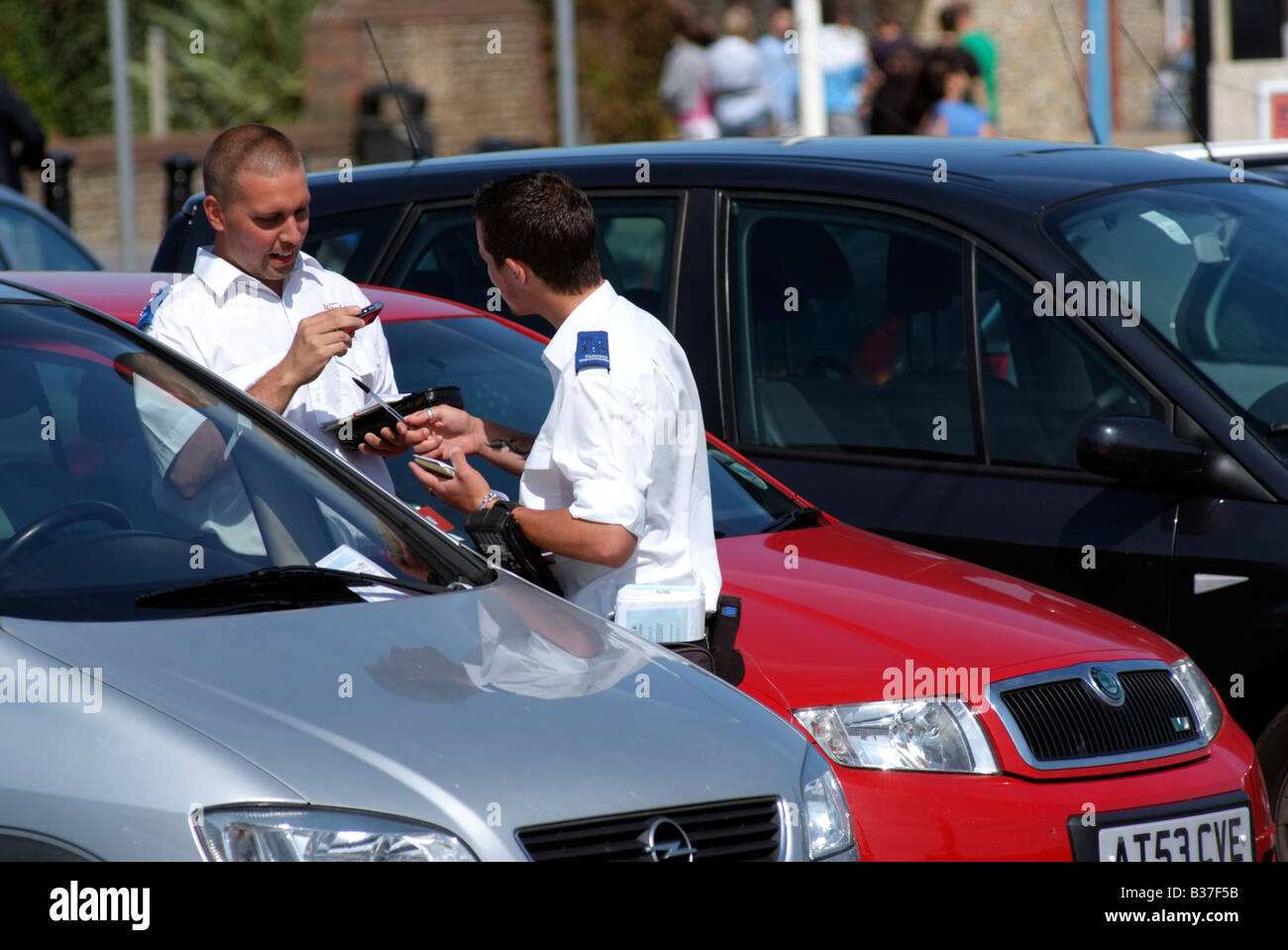 Civil parking enforcement officer issue a penalty ticket Worthing on Sea West Sussex England UK NCP Services contract - Stock Image