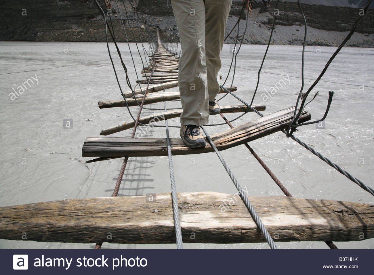 Person crossing suspension bridge over Hunza River, near Passu, Pakistan. - Stock Image
