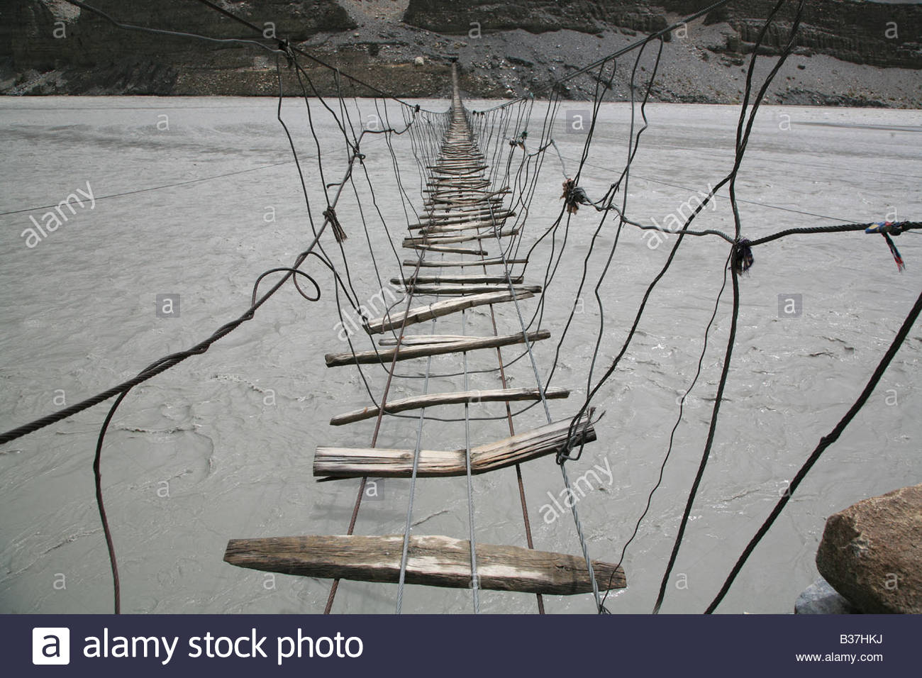 Footbridge over Hunza river, near Passu, northern Pakistan. - Stock Image