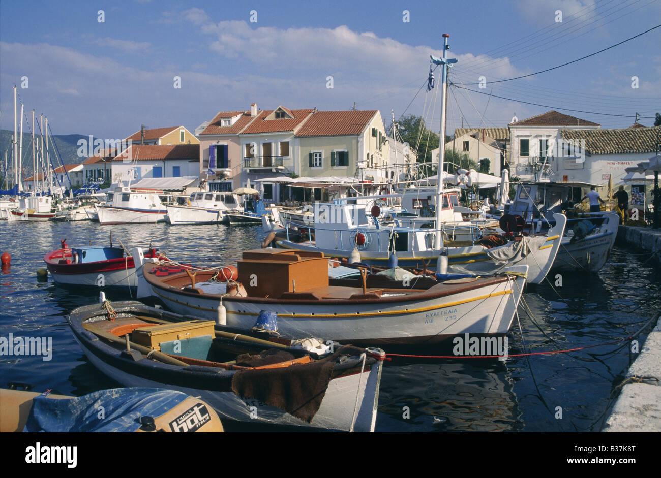 Cephallonia Ionian islands Fishing boats Motorboat Moored Building FISKARDHO KEFALLONIA GREECE - Stock Image