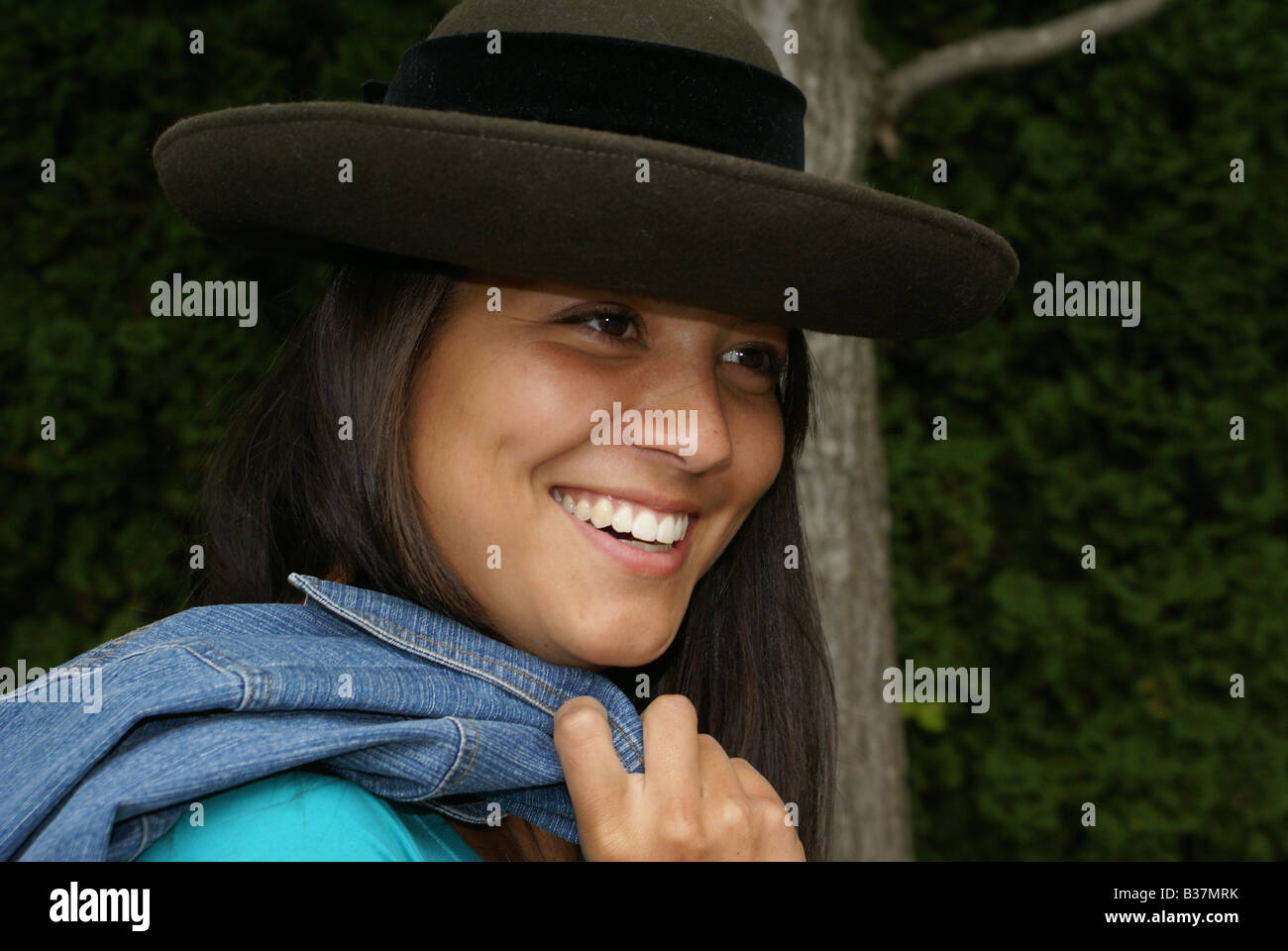 5228ffe7d American/Japanese teenager posing with hat and jean jacket outside - Stock  Image