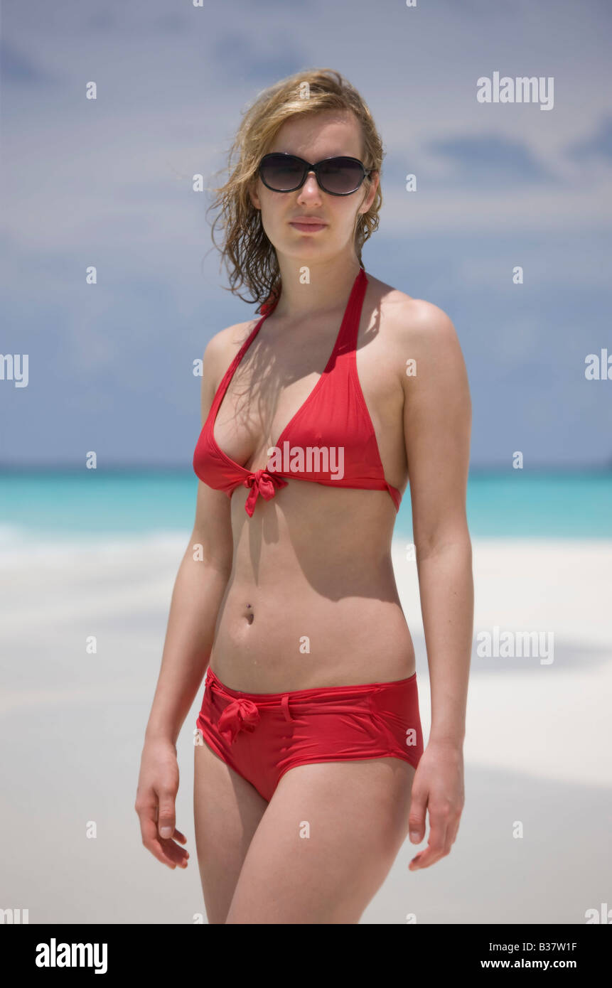 Young woman looking at camera on deserted white sand beach surrounded by tropical waters in Maldives near India - Stock Image