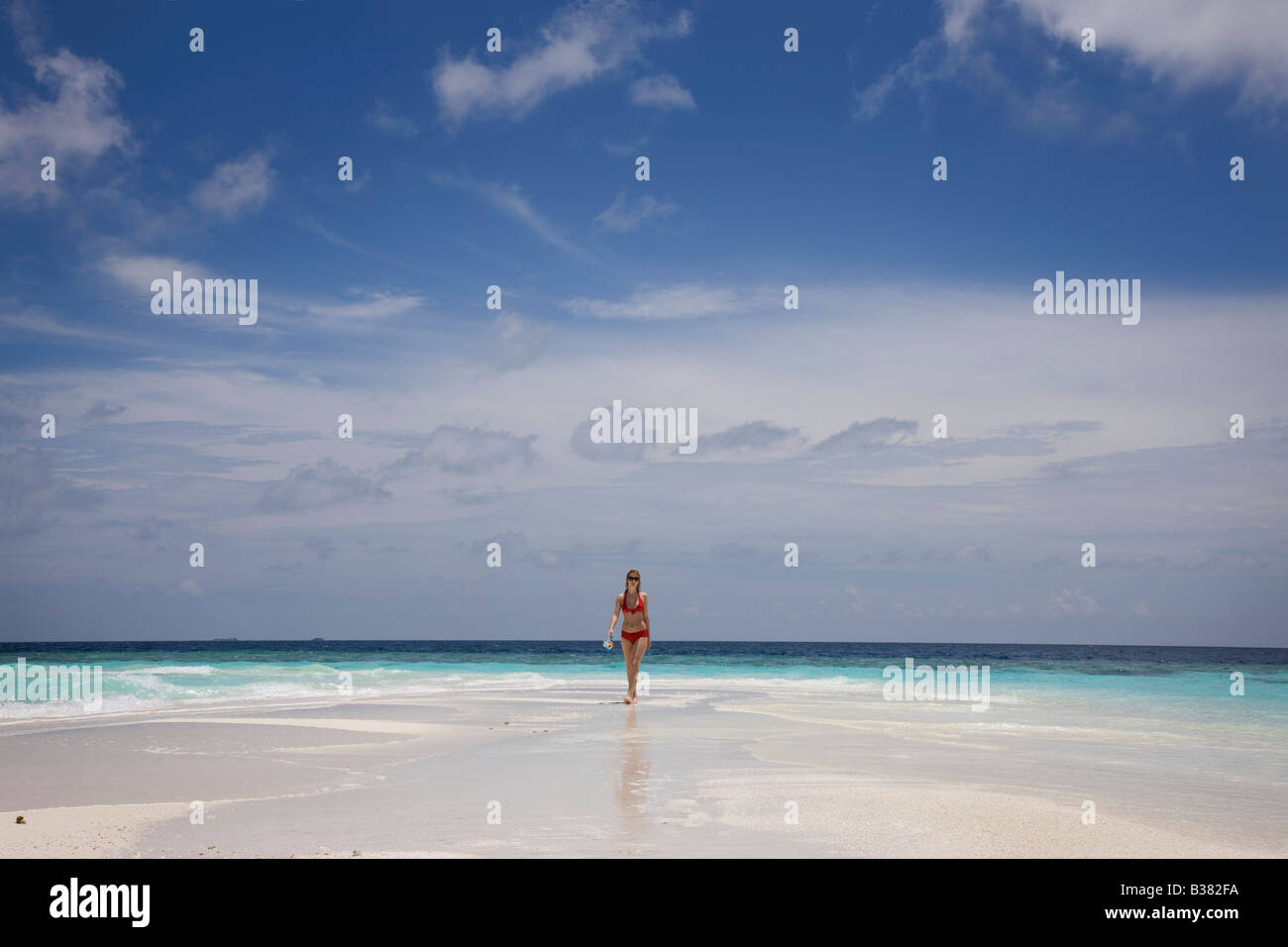 Young woman walking along deserted white sand beach surrounded by tropical waters in Maldives near India - Stock Image