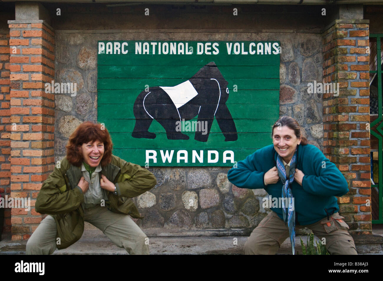 VISITORS clown around in front of the sign to VOLCANOES NATIONAL PARK RWANDA AFRICA - Stock Image