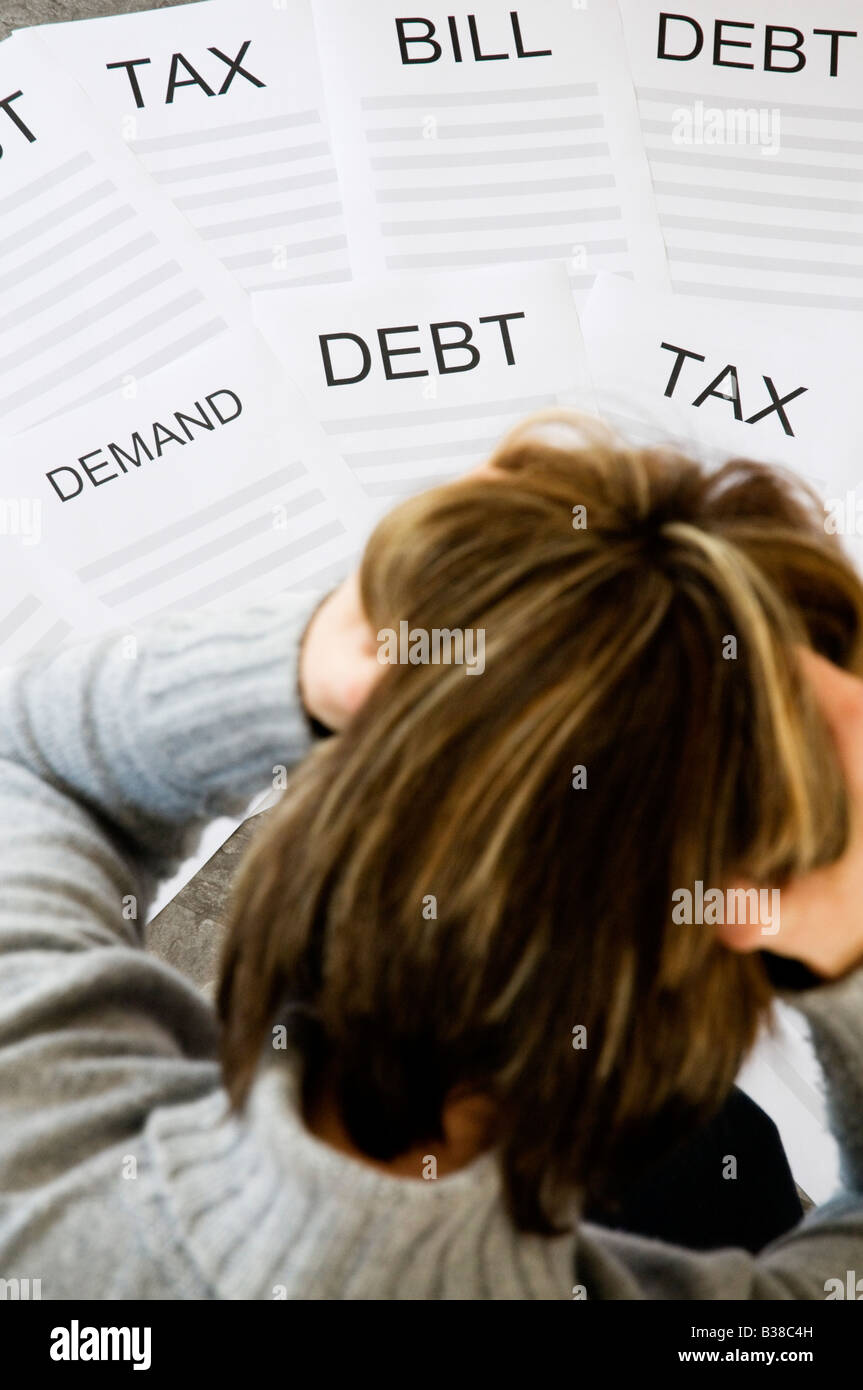 Woman with head in hands worrying about household debt and bills - Stock Image