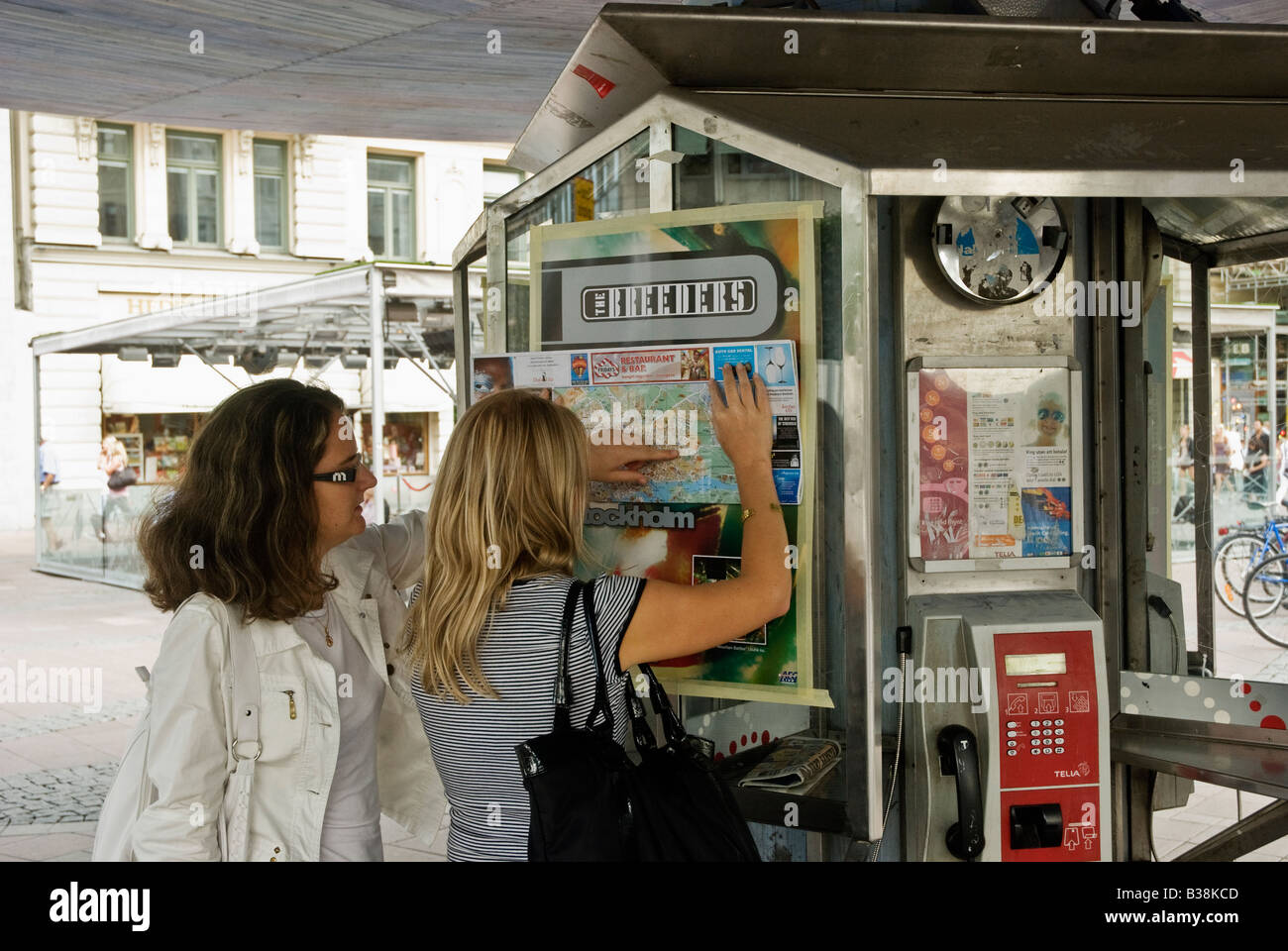 Two female tourist in downtown at Stureplan consults a map over central Stockholm Sweden Stock Photo