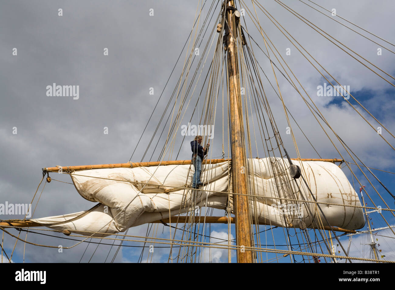 Person sorting ropes and sail high up on square rigged mast on boat in Tall Ships race sailor working - Stock Image